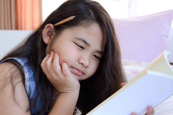 girl-squints-reading-in-bed-660x440